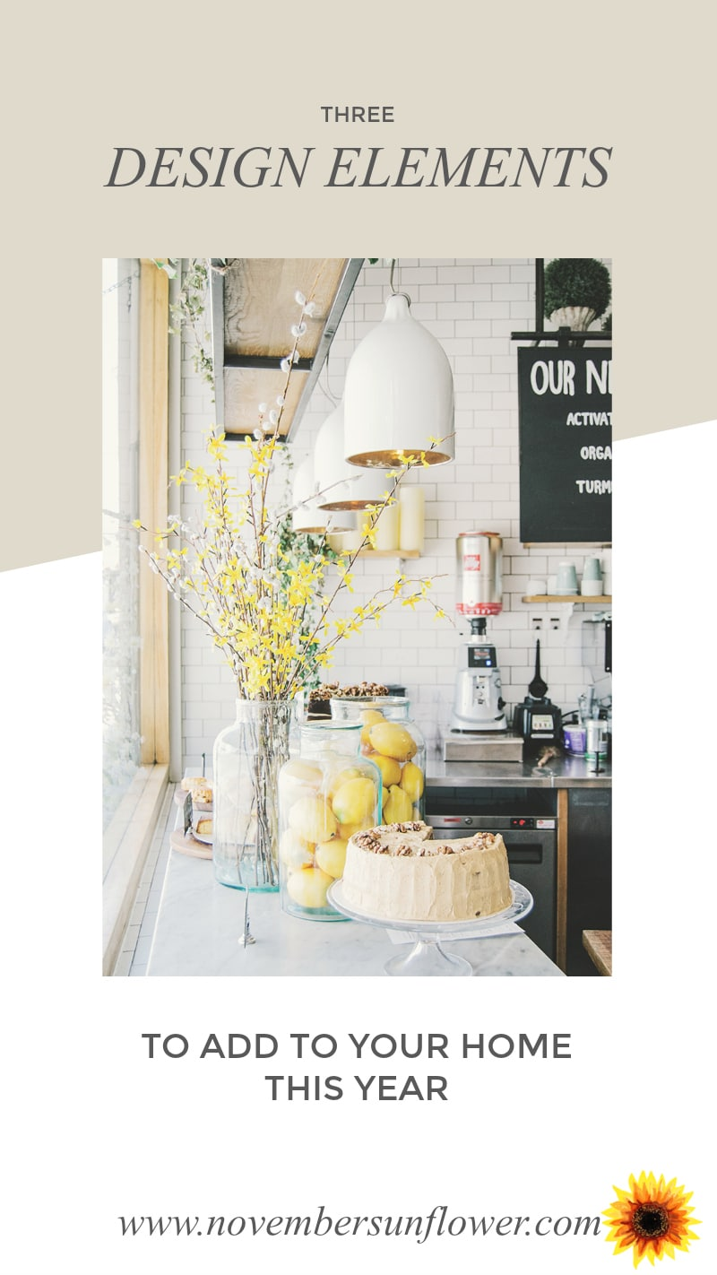 Kitchen counter with display of cake and flower. Background subway tiles.