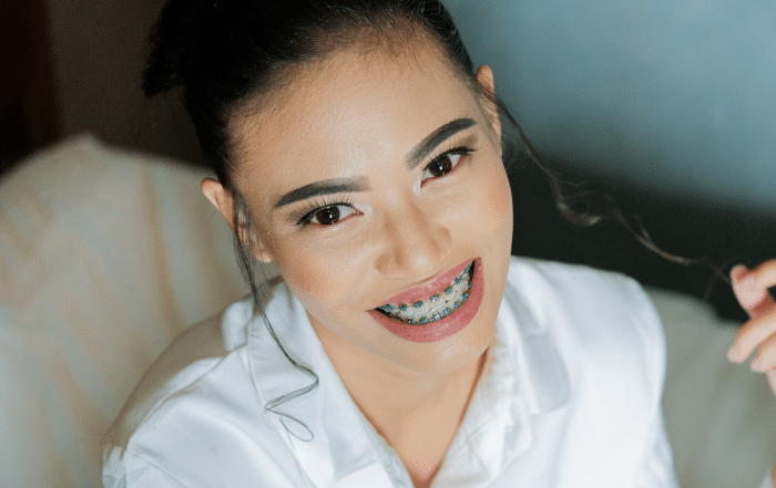 dark haired woman smiling with braces on teeth